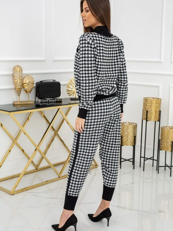 is decorated with black ribbons on the sleeves and at the bottom of the legs and eye-catching golden buttons. A set that you can easily combine with